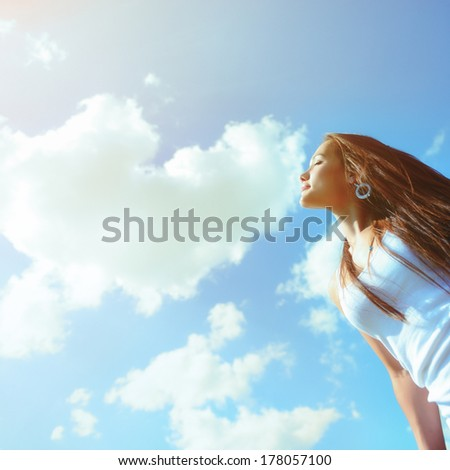 Happy fresh girl enjoying summer, youth and freedom. Toned outdoor shot against blue sky.