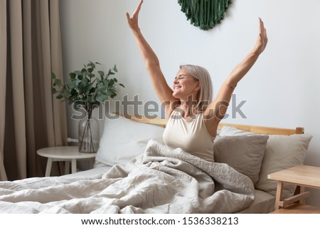 Happy fresh mature middle aged woman stretching in bed waking up alone happy concept, smiling old senior lady awake after healthy sleep sitting in cozy comfortable bedroom interior enjoy good morning