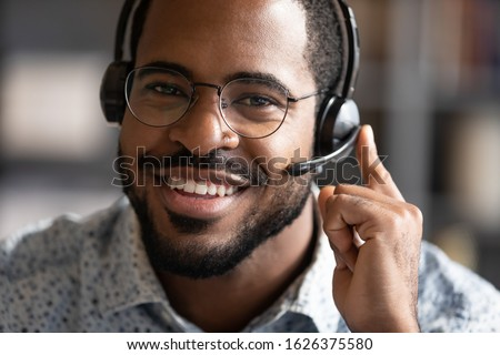 Happy friendly african ethnic business man telemarketing operator wear wireless headset microphone looking at camera, customer support service assistant on call center phone closeup headshot portrait Сток-фото ©