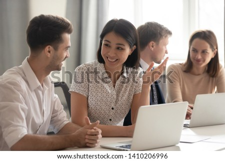 Happy friendly diverse employees talking laughing working together discussing good news joking sitting with coworkers laptops, smiling office workers having fun sharing ideas chatting at work break