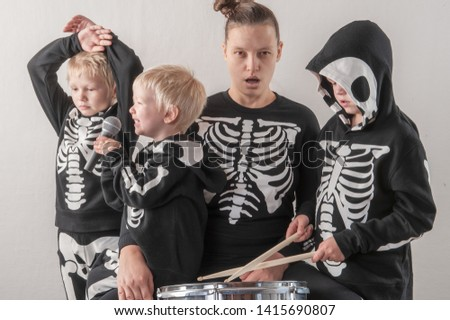 Happy friendly family of musicians in carnival costumes, boys and young mother play drum and try to sing with microphone. Black suit with image of skeletons. Classic halloween costume. Funny children #1415690807