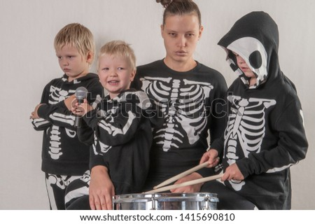 Happy friendly family of musicians in carnival costumes, boys and young mother play drum and try to sing with microphone. Black suit with image of skeletons. Classic halloween costume. Funny children #1415690810