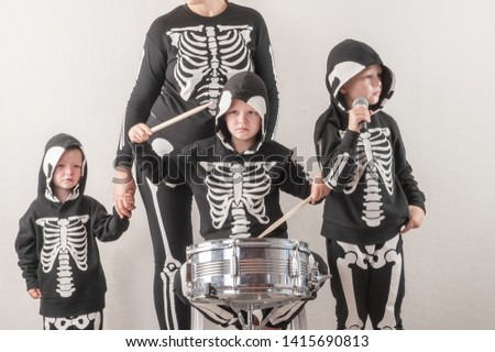Happy friendly family of musicians in carnival costumes, boys and young mother play drum and try to sing with microphone. Black suit with image of skeletons. Classic halloween costume. Funny children #1415690813