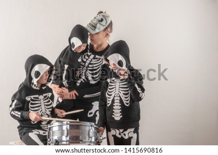 Happy friendly family of musicians in carnival costumes, boys and young mother play drum and try to sing with microphone. Black suit with image of skeletons. Classic halloween costume. Funny children #1415690816