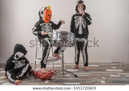 Happy friendly family of musicians in carnival costumes, boys and young mother play drum and try to sing with microphone. Black suit with image of skeletons. Classic halloween costume. Funny children #1415720603