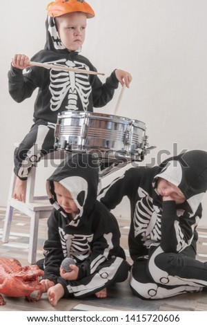 Happy friendly family of musicians in carnival costumes, boys and young mother play drum and try to sing with microphone. Black suit with image of skeletons. Classic halloween costume. Funny children #1415720606