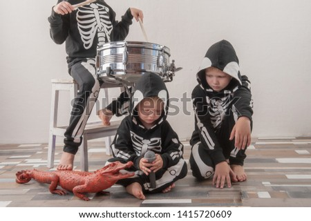 Happy friendly family of musicians in carnival costumes, boys and young mother play drum and try to sing with microphone. Black suit with image of skeletons. Classic halloween costume. Funny children #1415720609