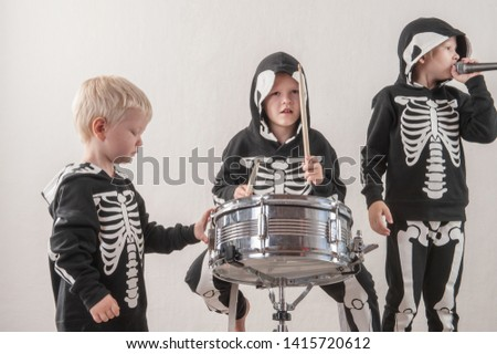 Happy friendly family of musicians in carnival costumes, boys and young mother play drum and try to sing with microphone. Black suit with image of skeletons. Classic halloween costume. Funny children #1415720612