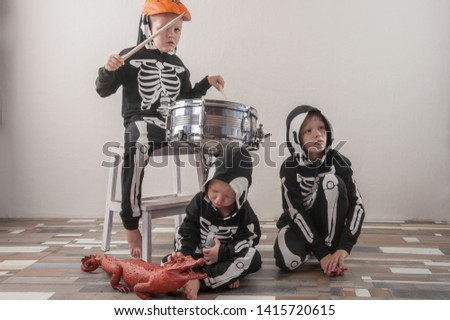 Happy friendly family of musicians in carnival costumes, boys and young mother play drum and try to sing with microphone. Black suit with image of skeletons. Classic halloween costume. Funny children #1415720615