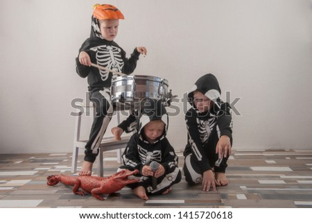 Happy friendly family of musicians in carnival costumes, boys and young mother play drum and try to sing with microphone. Black suit with image of skeletons. Classic halloween costume. Funny children #1415720618