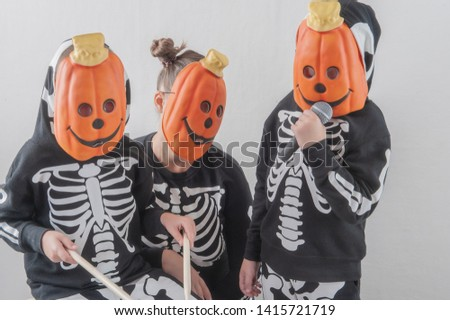 Happy friendly family of musicians in carnival costumes, boys and young mother play drum and try to sing with microphone. Black suit with image of skeletons. Classic halloween costume. Funny children #1415721719