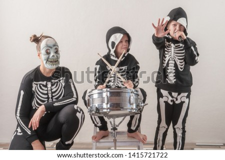 Happy friendly family of musicians in carnival costumes, boys and young mother play drum and try to sing with microphone. Black suit with image of skeletons. Classic halloween costume. Funny children #1415721722