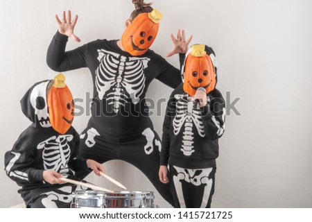 Happy friendly family of musicians in carnival costumes, boys and young mother play drum and try to sing with microphone. Black suit with image of skeletons. Classic halloween costume. Funny children #1415721725