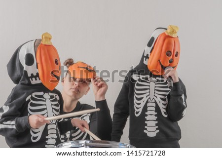 Happy friendly family of musicians in carnival costumes, boys and young mother play drum and try to sing with microphone. Black suit with image of skeletons. Classic halloween costume. Funny children #1415721728