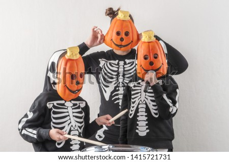Happy friendly family of musicians in carnival costumes, boys and young mother play drum and try to sing with microphone. Black suit with image of skeletons. Classic halloween costume. Funny children #1415721731
