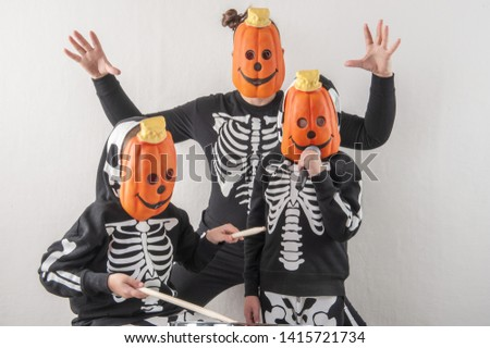 Happy friendly family of musicians in carnival costumes, boys and young mother play drum and try to sing with microphone. Black suit with image of skeletons. Classic halloween costume. Funny children #1415721734