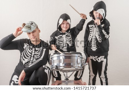 Happy friendly family of musicians in carnival costumes, boys and young mother play drum and try to sing with microphone. Black suit with image of skeletons. Classic halloween costume. Funny children #1415721737