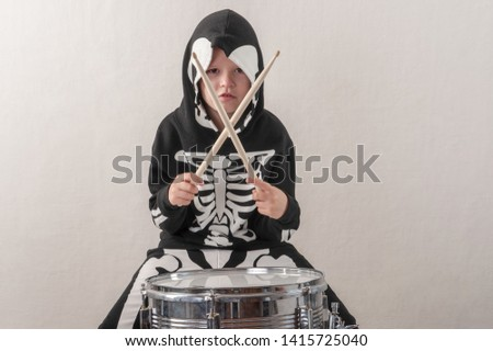Happy friendly family of musicians in carnival costumes, boys and young mother play drum and try to sing with microphone. Black suit with image of skeletons. Classic halloween costume. Funny children #1415725040