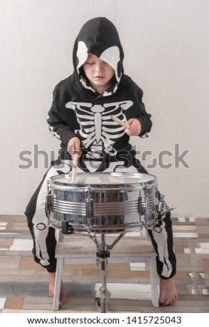 Happy friendly family of musicians in carnival costumes, boys and young mother play drum and try to sing with microphone. Black suit with image of skeletons. Classic halloween costume. Funny children #1415725043