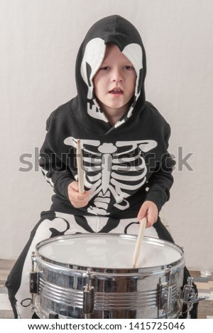 Happy friendly family of musicians in carnival costumes, boys and young mother play drum and try to sing with microphone. Black suit with image of skeletons. Classic halloween costume. Funny children #1415725046