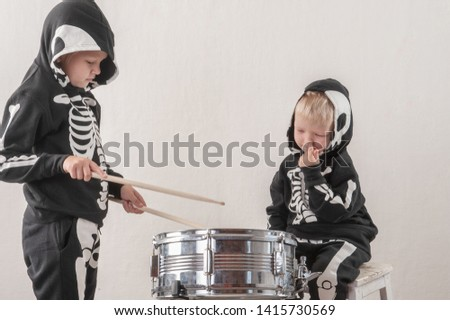 Happy friendly family of musicians in carnival costumes, boys and young mother play drum and try to sing with microphone. Black suit with image of skeletons. Classic halloween costume. Funny children #1415730569