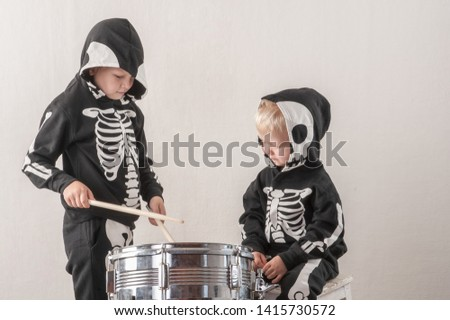 Happy friendly family of musicians in carnival costumes, boys and young mother play drum and try to sing with microphone. Black suit with image of skeletons. Classic halloween costume. Funny children #1415730572