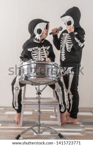 Happy friendly family of musicians in carnival costumes, boys play drum and try to sing with microphone. Black suit with image of skeletons. Classic halloween costume. Funny children #1415723771