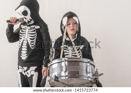 Happy friendly family of musicians in carnival costumes, boys play drum and try to sing with microphone. Black suit with image of skeletons. Classic halloween costume. Funny children #1415723774