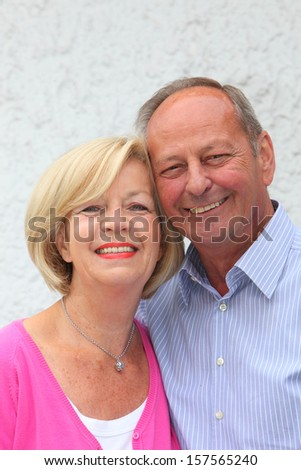 Happy friendly senior couple posing arm in arm with their faces touching smiling at the camera - stock photo