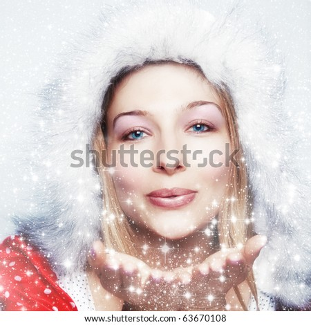 Happy friendly woman blowing snowflakes in winter season