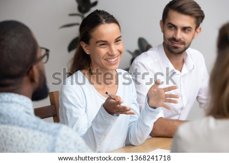 Happy friendly woman team leader coach mentor talking to employees group at office meeting smiling offering idea teaching interns or reporting at briefing seminar having fun business conversation #1368241718