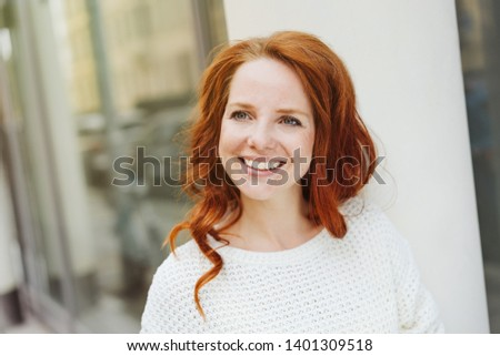 Happy friendly young redhead woman in an urban street looking to the side with a smile and interested expression