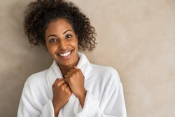 Happy friendly young woman in white bath robe looking at camera isolated on beige background with copy space. Portrait of african american girl in bathrobe after body treatment. Girl after shower.