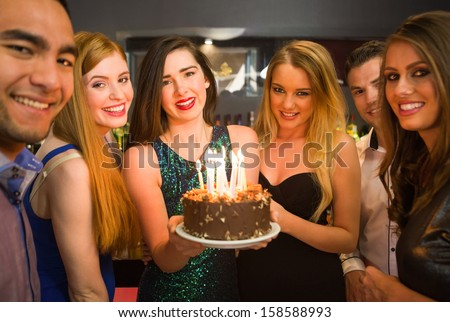 Happy Friends Celebrating Brithday One Holding Birthday Cake Looking At Camera In A Nightclub