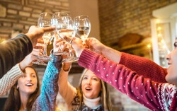 Happy friends celebrating Christmas toasting champagne wine at home dinner - Winter holiday concept with young people enjoying time together having fun at log cabin - Warm filter with focus on glasses
