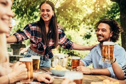 Happy friends celebrating drinking beer pint at park outdoor - Young people talking and laughing together at brewery pub garden - Friendship, youth and beverage concept