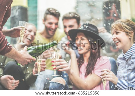 Shutterstock Happy friends celebrating drinking champagne and making party outdoor - Young loud people having fun outside - Youth and fest concept - Focus on left man hand with bottle - Warm contrast filter