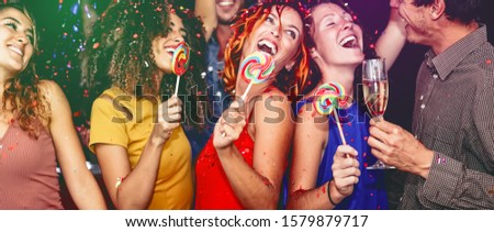 Happy friends celebrating new year eve drinking champagne in nightclub - Young people having fun dancing with lollipops in disco club - Youth culture entertainment lifestyle and nightlife concept #1579879717