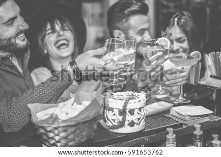 Happy friends cheering at cocktail jazz bar - Young trendy people having fun drinking alcohol and laughing - Party concept - Focus on left man - Black and white editing