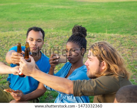 Happy friends cheering with beer and taking pictures. Group of young people relaxing after work. Celebration concept