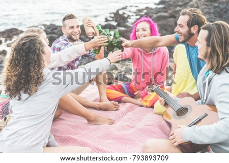 Happy friends cheering with beers and playing music in camping outdoor - Trendy people having fun together doing pic-nic - Friendship, youth lifestyle and vacation concept - Focus on hands bottles
