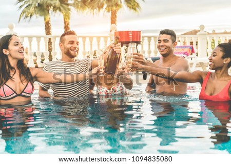 Happy friends cheering with champagne in pool party at sunset - Rich people having fun in exclusive tropical vacation outdoor- Holiday, youth lifestyle and friendship concept - Focus on men faces #1094835080