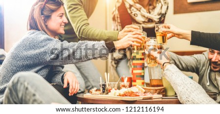 Happy friends cheering with half pints beer in pub restaurant - Young people having fun playing board games at vintage trendy pub party - Youth, vacation and nightlife concept - Focus on bottom hand