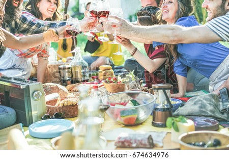 Happy friends cheering with wine glasses at pic-nic lunch outdoor - Young students having fun doing a toast and eating on nature - Food and youth concept - Focus on center glasses - Vintage filter