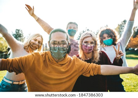 Happy friends covered by face masks having fun in the park - New normal concept with young people having party together outside.