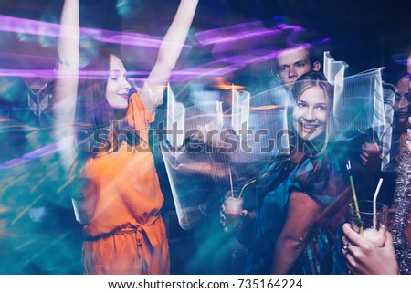 Happy friends dance party in motion. Joyful New Year company in night club, active Christmas celebration. Disco people in blurred colors, modern youth life #735164224