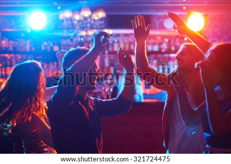 Happy friends dancing at party in bar #321724475