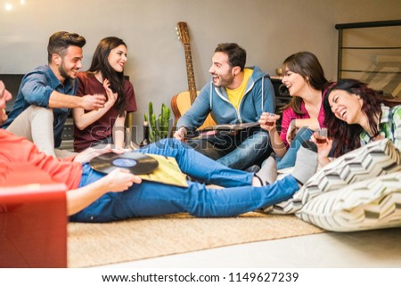 Happy friends doing party listening vintage vinyl disc albums - Young millennials people having fun drinking shots and laughing together - Youth and winter fest concept - Focus on right man face