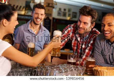 Happy friends drinking beer at counter in pub, chatting with female bartender, smiling. #139816456