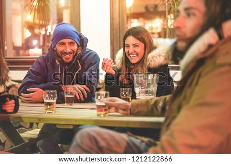 Happy friends drinking beers at trendy chalet pub restaurant in mountains on evening time - Young people having fun in winter vacation - Friendship and youth concept - Soft focus on woman face